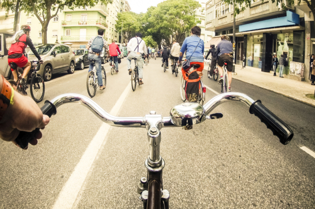A group of bicycle riders taking the streets during a collective ride promoting the use of bicycles as a mode of transportation in the city of Lisbon.